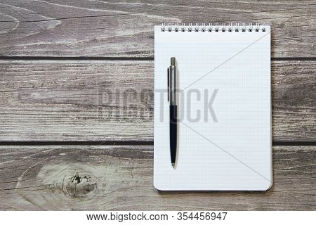 Notepad With A Blank White Sheet In A Checker Paper With Ball Pen Lies On The Background Of Wooden B
