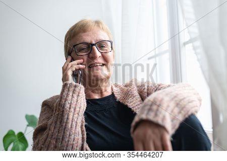 Senior Woman Speaking On Cell Phone. Senior Woman Speaking On Cell Phone And Laughing. Happy Pension