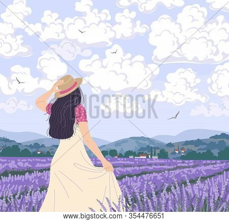 Young Woman Enjoys The Scenery Of Lavender Field. Dreamy Girl In Straw Hat Walking Among Purple Flow