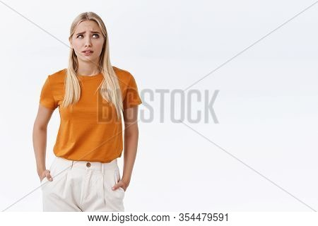 Confused, Puzzled Cute Clueless Blond Girl In Orange T-shirt, Hold Hands In Pockets, Furrow Eyebrows