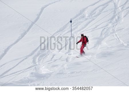 Snowboarder In Red Descends On Snowy Ski Slope After Snowfall At Cold Winter Day