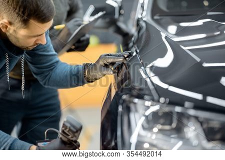 Car Service Worker Examining Vehicle Body For Scratches And Damages, Taking A Car For Professional A