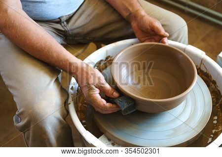 Professional Potter Working At Kick Wheel In Home Studio. Handmade Mastery Concept. Artisan At Works