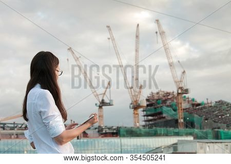 Architect On The Construction Site Makes Supervision. Young Woman Engineer Or A Businessman In The F