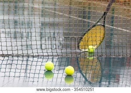Yellow Tennis Balls On Hard Court In Raining Weather. Racquet Leaning On Net And Wet Tennis Balls On