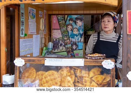 Takayama, Japan - April 26, 2014: Saleswoman Inside His Senbei Store At The Miyagawa Morning Market.