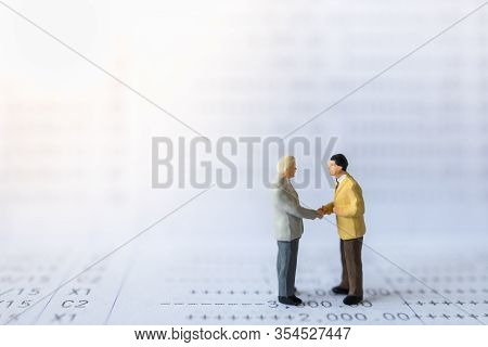 Business, Money, Financial And Cooperation Concept. Close Up Of Two Businessman Miniature Figures Pe