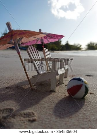 A Photo Of Miniature White Adirondack Chairs And Umbrellas And A Colorful Beach Ball On A Beach