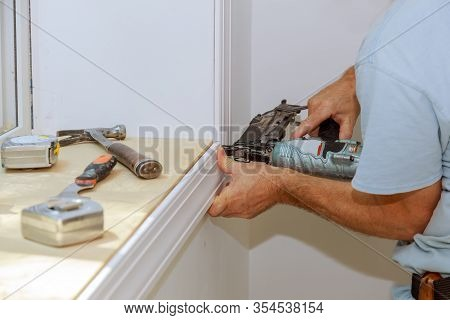 Worker Installing Trim Around A Window Molding Installed Moldings Materials