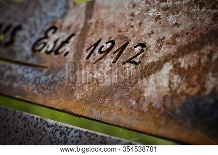 Rusting Dated Sign Outside An Historical Site