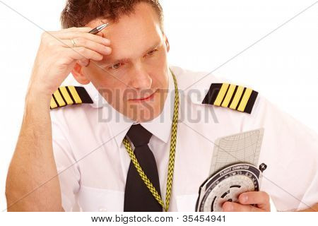 Airline pilot wearing shirt with epaulets and tie using flight computer for navigation calculations, filling in and checking papers flight plan.