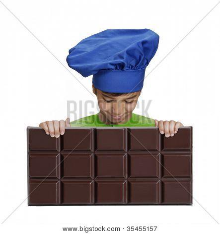 Little boy chef holding a big chocolate bar,Little kid holding chocolate.