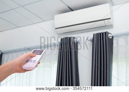 Human Hand Controling Air Conditioner In Room.