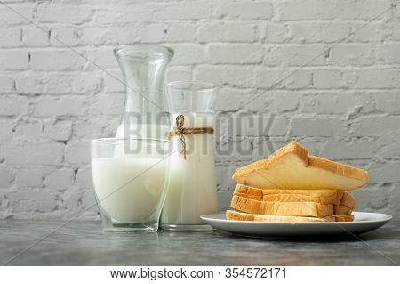 Breakfast Table With Glass Of Milk And Slice Bread On Kitchen Table.