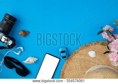 Flat Lay Traveller Accessories On Blue Background With Copy Space.