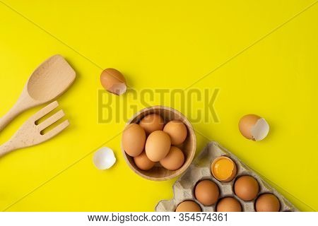 Fresh Eggs On Wooden Plate And Kitchenware On Yellow Background.