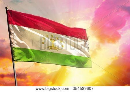Fluttering Tajikistan Flag On Beautiful Colorful Sunset Or Sunrise Background. Tajikistan Success An