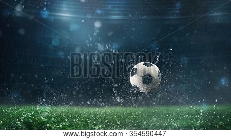 Close Up Of A Soccer Ball Rolling On The Playing Field On A Rainy Night