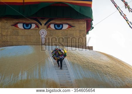 A Man Climbing The Face Of The Bhouddha Stupa Carrying A Load Of Prayer Flags In Kathmandu, Nepal.