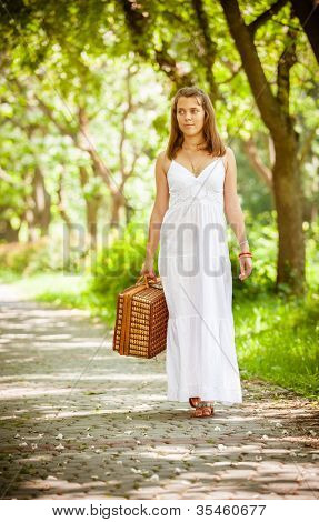 Lonely girl with suitcase at park