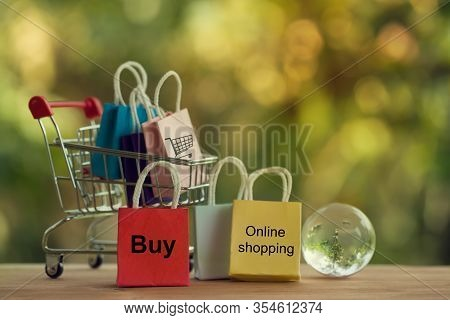 Shopping Online And E-commerce Concept: Paper Bag In A Shopping Cart And Crystal Globe. Online Store