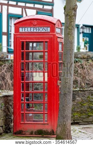Red English Telephone Booth In Front Of A Stone Wall In Bad Muenstereifel, Germany