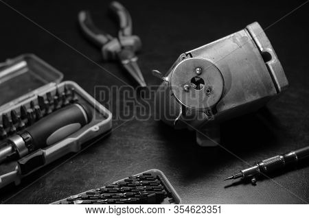 Screw Pencil Sharpener And Tool. Old Pencil Sharpener And Hand Tools On A Black Background. Repair O