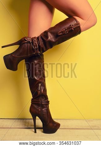 Woman In Brown Boots Stands Cross-legged Near Yellow Wall
