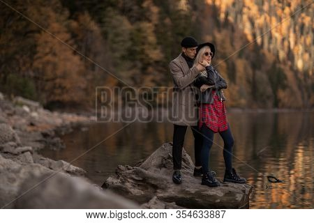 A Man Hugs A Woman Near A Lake. Couple Of Lovers Stand Together Near A Mountain Lake