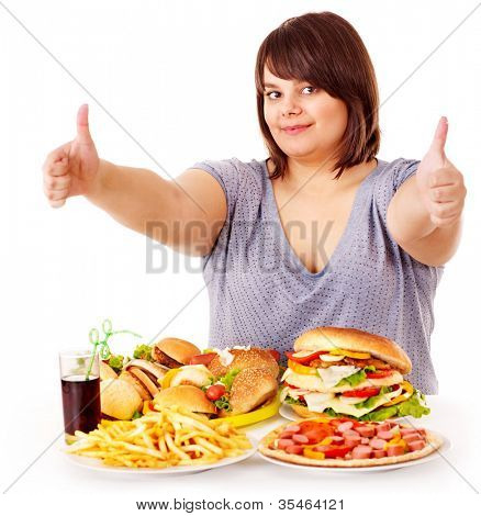 Happy overweight woman eating fast food.