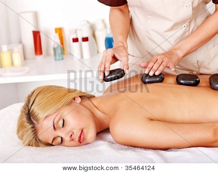 Satisfied blond woman getting massage in spa.