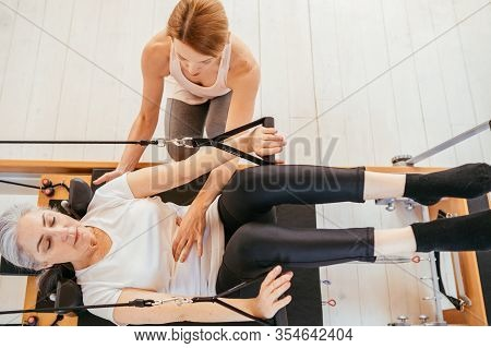 Woman Practicing Stretching Exercise With Personal Trainer On Reformer In Gym. Top View Of Elderly G