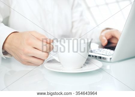 Sideview Of Businessman Hands Typing On Laptop  On Office Desktop With Cup Of Coffee