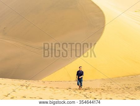 Single Young Asian Man Walks The Edge Of Sand Dune In Desert At Mingsha Mountain And Crescent Moon S