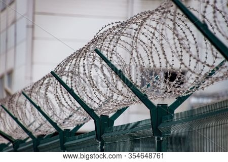 Swirls Of Barbed Wire Over The Fence. The Fence Symbolizes Prison, Non-freedom, Totalitarianism And