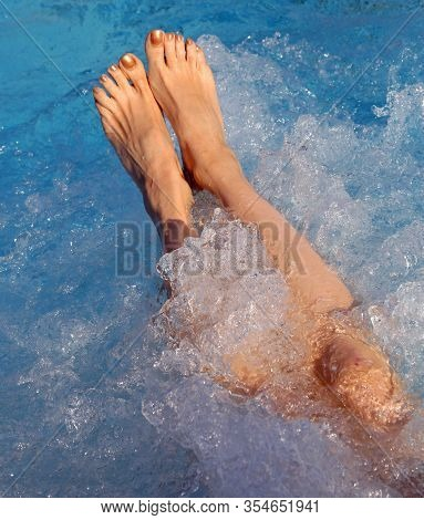 Feet Of Young Woman During The Whirlpool Therapy In The Spa Pool
