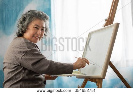 Happy Smiling Asian Elderly Woman Oil Painting On Canvas At House On Holidays. Artist Senior Female