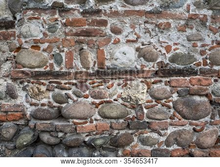 The Ancient Wall Is Lined With Bricks Of Various Sizes And Large Cobblestones. Bricks And Cobbleston
