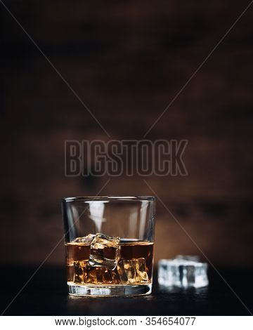 Whisky, Whiskey, Bourbon Or Cognac With Ice Cudes On Black Stone Table And Wood Background