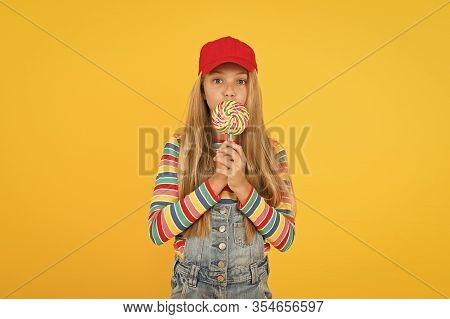 Yummy Dessert. Small Child Licking Candy Dessert On Yellow Background. Little Girl Prefer Sweet Dess