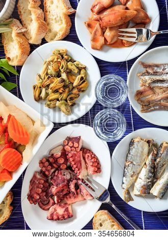 Cold Ouzo, Raki Alcohol With Seafood Meze On White Dishes. Two Glasses And Various Healthy Mollusks