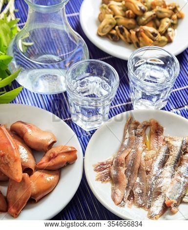 Ouzo, Raki Alcohol With Seafood Meze On White Dishes. Two Glasses And Various Healthy Mollusks Backg