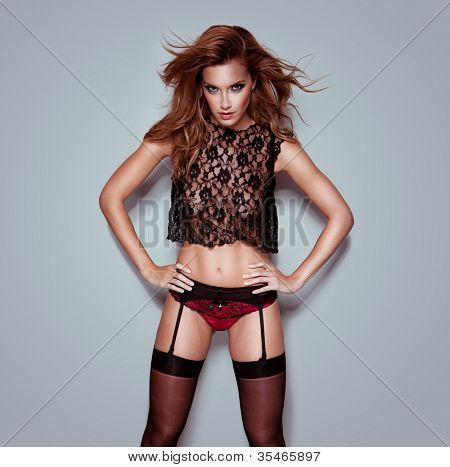 Provocative woman with in intense sultry look standing with her hands on her hips in in lace, lingerie and suspenders
