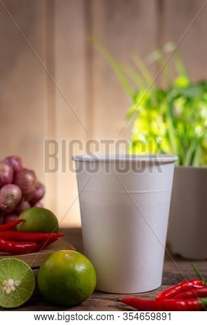 Cup Of Noodle With Lime And Chili And Onion And Vegetable On Wooden Table Blurred Background