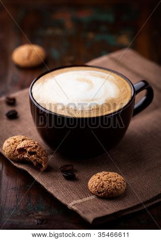 Cup of cafe au lait and biscotti on the table