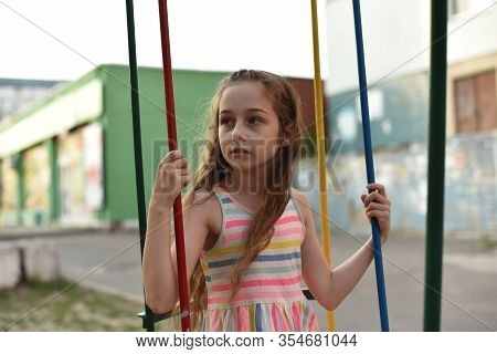 Swing Ride - Swinging Girl. Girl Riding A Swing. A Girl Of 9 Years Old Rides A Swing In The Yard In