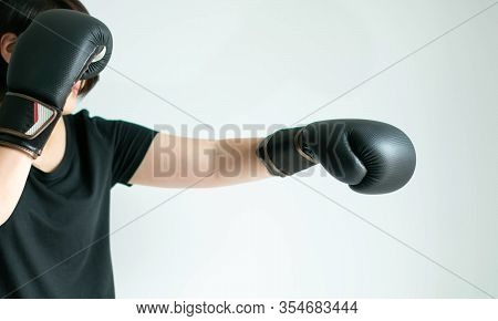 Close-up Side View Of A Woman In A Black T-shirt And Black Boxing Gloves Stretching Her Left Fist Fo