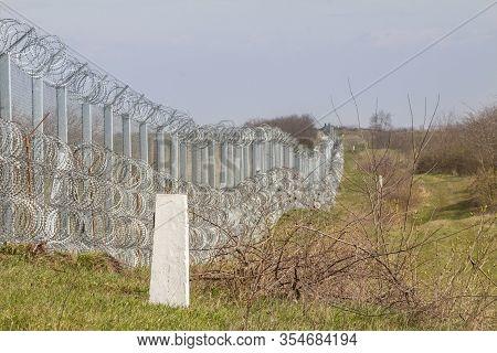 Border Fence Between Rastina (serbia) & Bacsszentgyorgy (hungary) With Boundary Marker. This Border