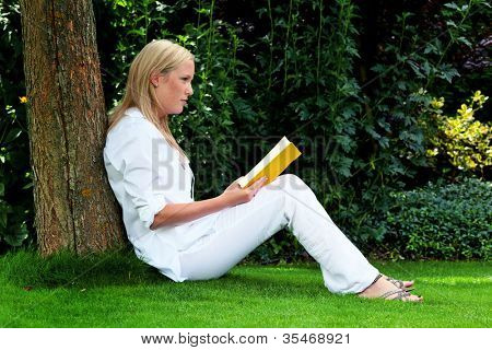 a young woman sitting on the grass and reading a book. recreation in the park