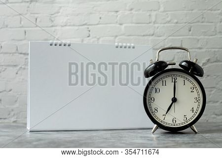 Classic Clock With Blank Calendar Note On Brickwall Background, View From Front Table.